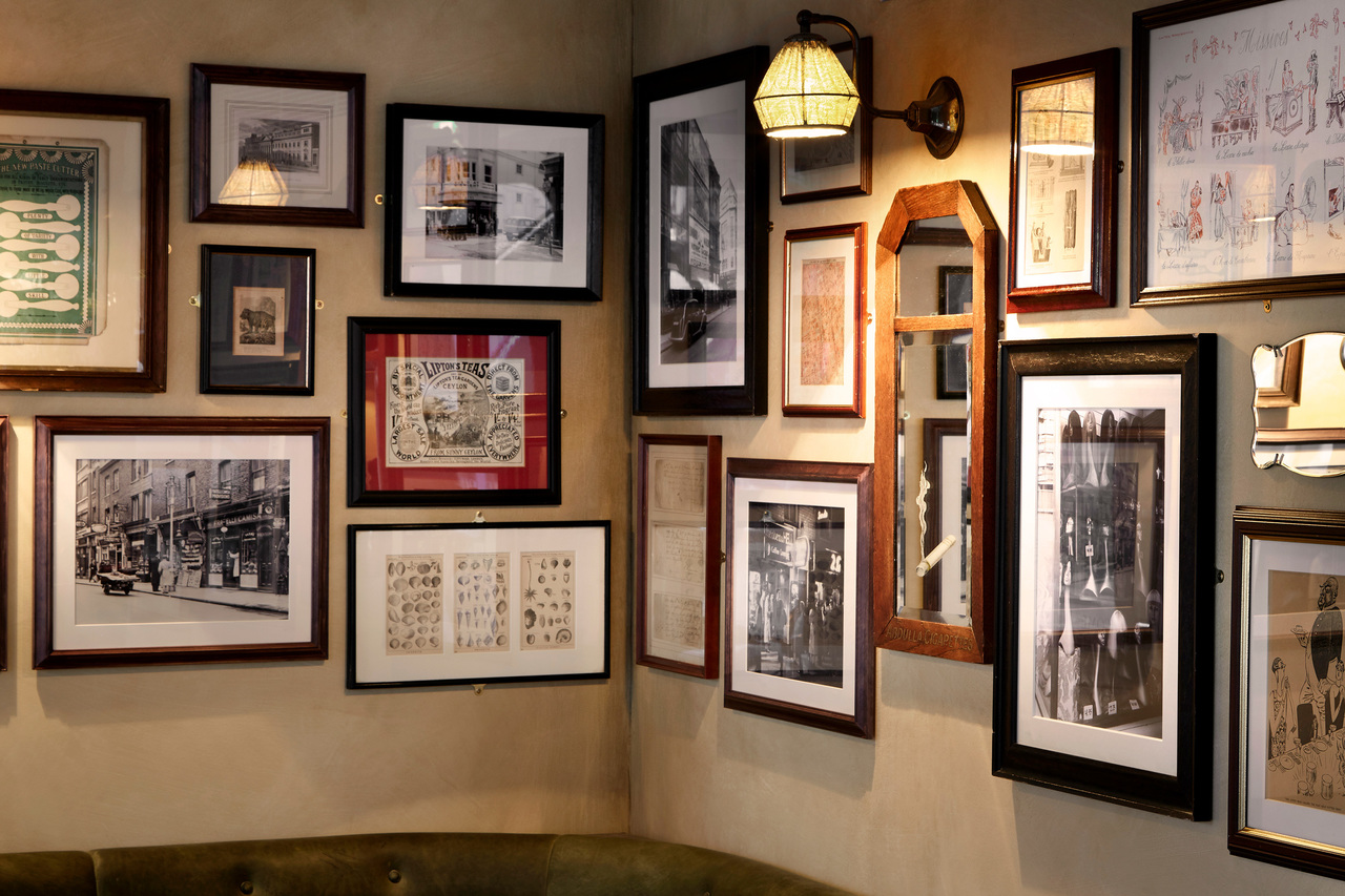 A wall with framed artwork and mirrors