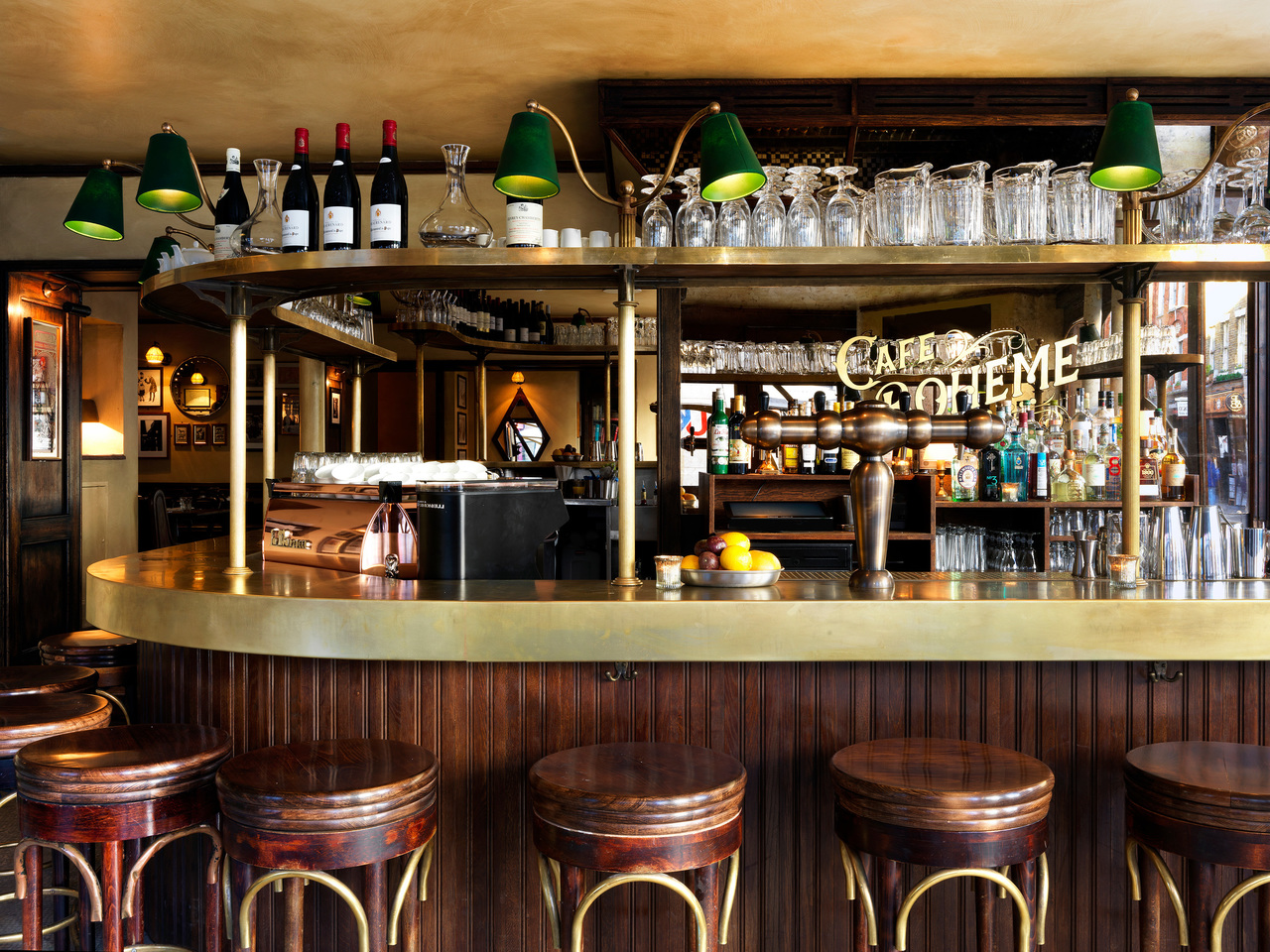 A wood and brass bar with wooden bar stools